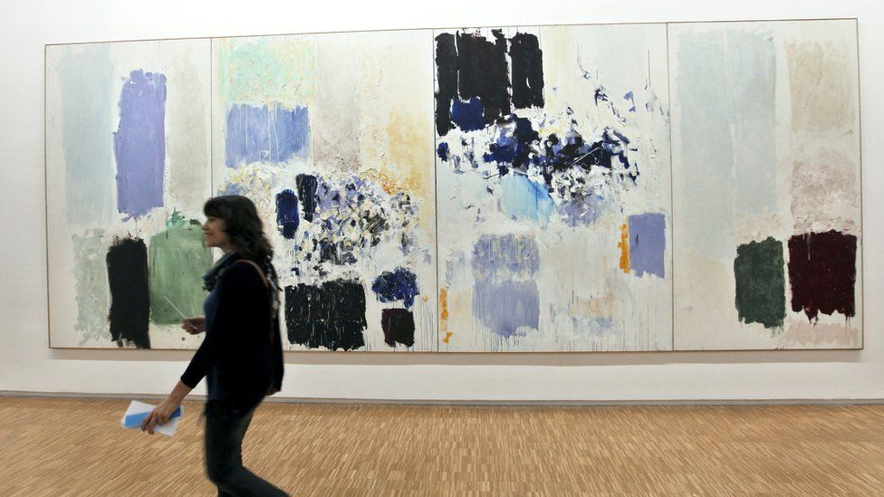 Visitor walking past a Joan Mitchell artwork