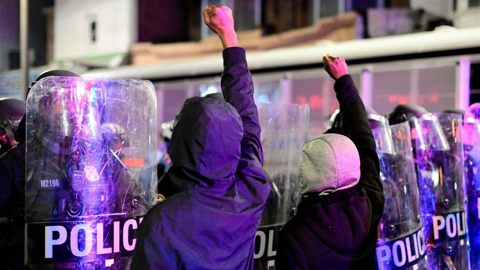 Demonstrators raise their fists in front of police officers during a rally after the death of Walter Wallace Jr., a Black man who was shot by police in Philadelphia, Pennsylvania, US, 27 October, 2020.