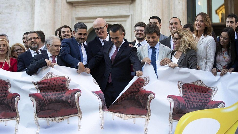 Italian Foreign Minister Luigi Di Maio (C), rips a banner with photos of MPs' armchairs exhibited by the M5S parliamentarians in front of the Chamber of Deputies in Rome, 8 October 2019