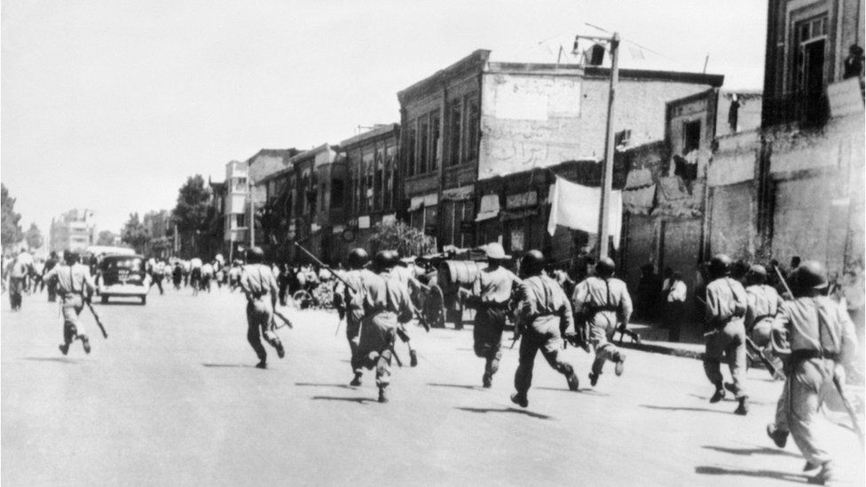 old photo of soldiers chasing rioters through the streets of Tehran