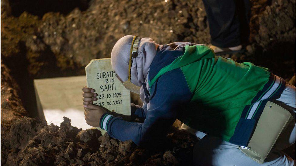 Seorang anggota keluarga yang mengenakan masker wajah berduka selama pemakaman kerabatnya