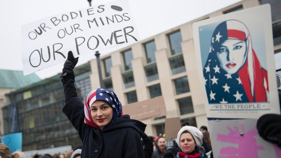 A Woman wearing a USA flag as a headscarf attends a protest for women's rights and freedom in solidarity with the Women's March on Washington in front of Brandenburger Tor on January 21, 2017 in Berlin, Germany.