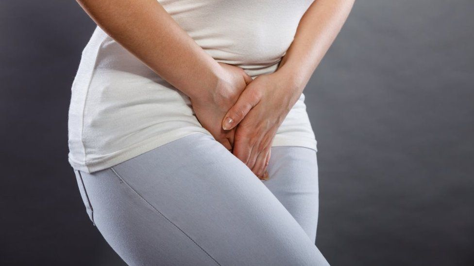 Stock image of a clothed woman holding her crotch area