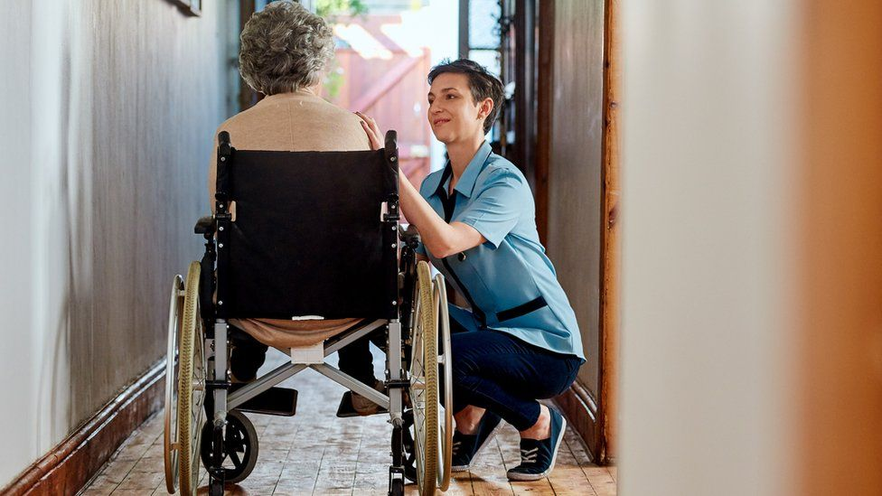Carer helps woman in wheelchair