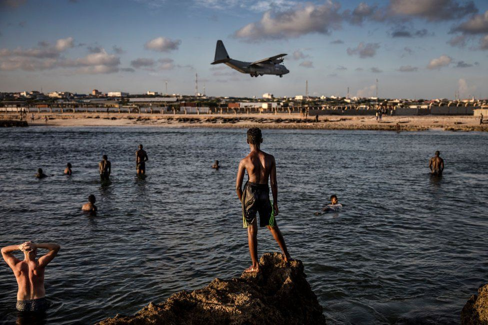 Soldiers and residents swim next to Mogadishu's air base as a plane flies overhead.