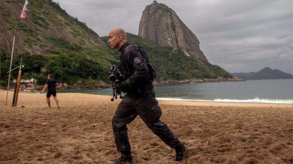 A member of the military police, patrols during a police operation in Vermelha beach at Urca neighbourhood, Rio de Janeiro, Brazil, on June 8, 2018
