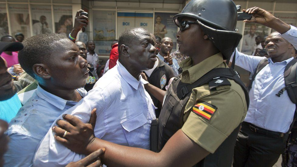 Opposition leader and presidential candidate Kizza Besigye, center, is grabbed by riot police after attempting to walk with his supporters along a street in downtown Kampala, Uganda Monday, Feb. 15, 2016.