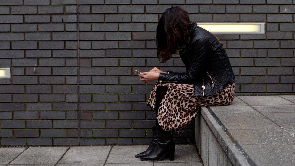 Woman on phone, sitting on step