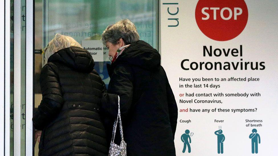Two women walk past a sign providing guidance information about novel coronavirus (COVID-19)