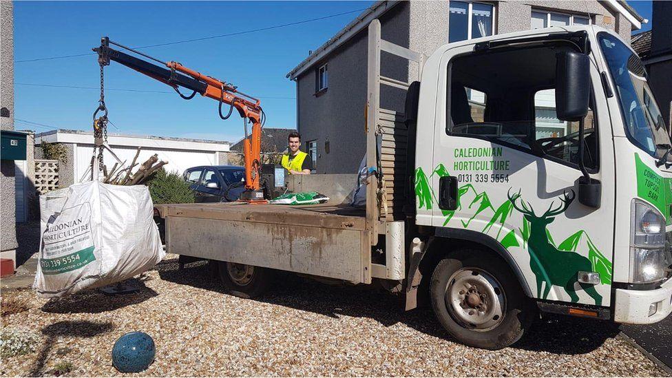 Low-loader picking up waste
