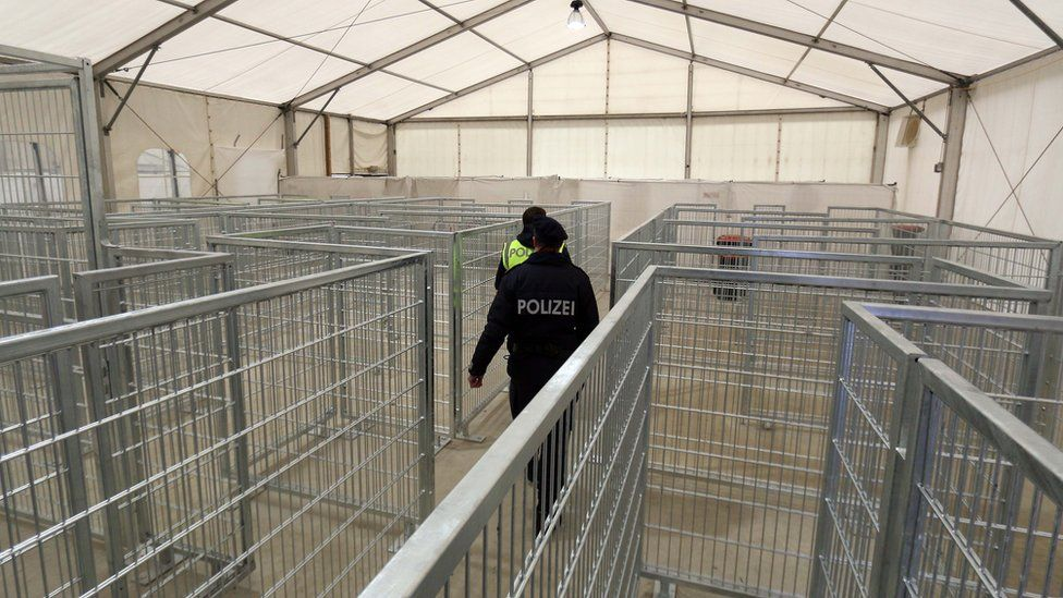 Two policeman walk in an empty registration tent for migrants at the border to Slovenia in Spielfeld, Austria