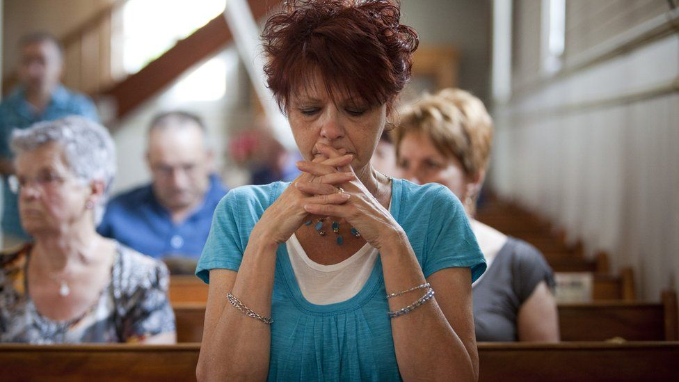 A woman attends Mass in 2013 to pray for the Lac-Megantic victims