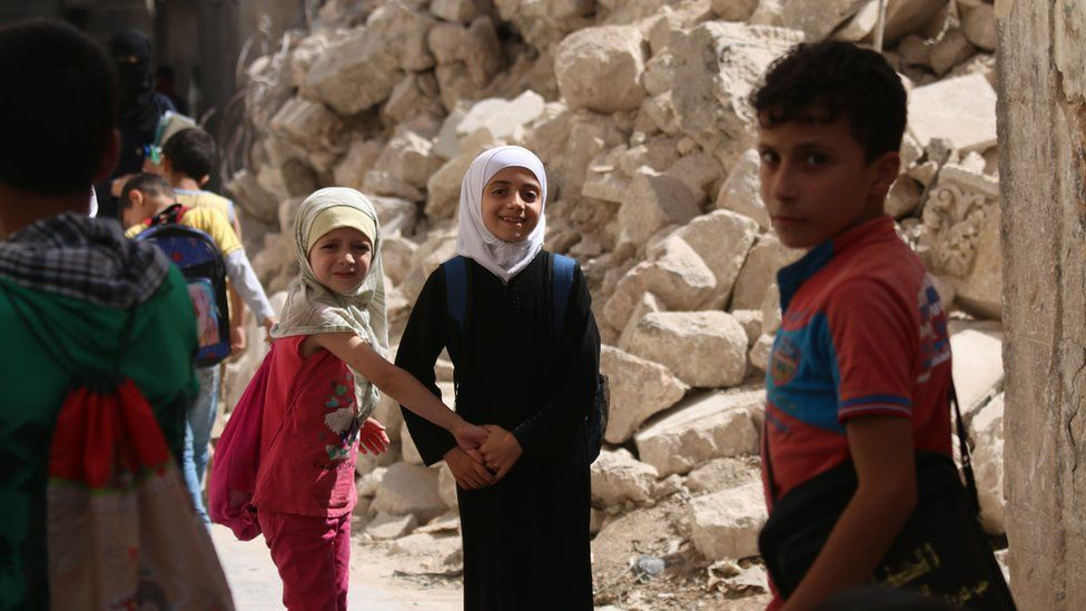 On 21 September 2016 in eastern Aleppo Judy (white head scarf), 9, and her schoolmates walk to school past the rubble of nearby houses.