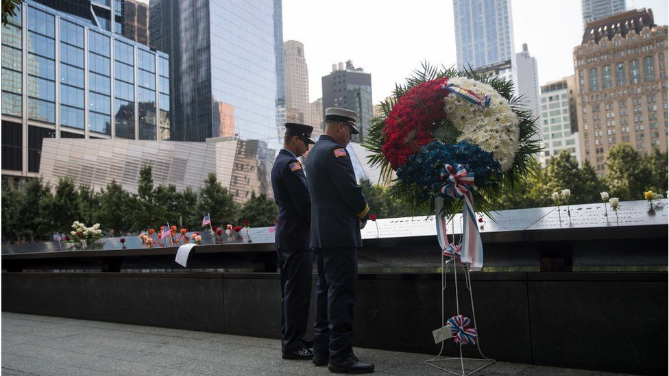 Two firefighters pay their respects during a commemoration ceremony for the victims of the September 11 terrorist attacks at the National September 11 Memorial