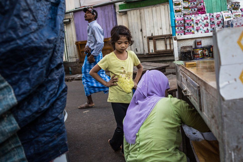 A young girl waits for Thwarhairah to exchange money at her betel nut stand in downtown Yangon, Myanmar, November 2014.