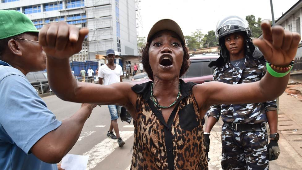 People celebrate outside the Court on March 26, 2018 in Freetown after Sierra Leone's High Court lifted an order that had halted the country's presidential runoff because of a complaint of electoral fraud backed by the ruling party