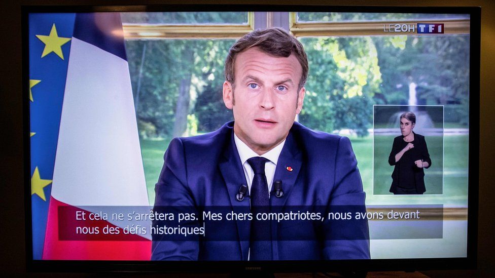 Emmanuel Macron delivering his address to the nation on a television screen