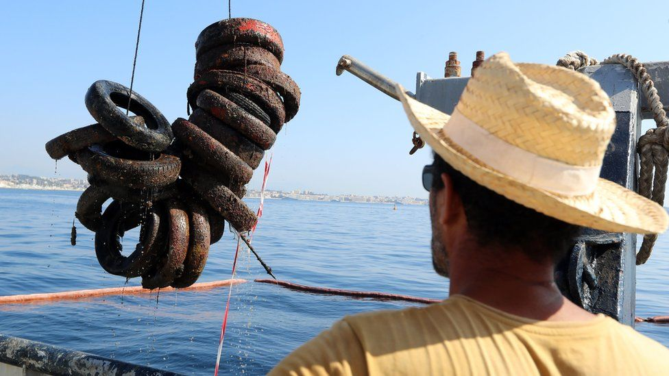 man in straw hat watching tyres being winched out of the sea by a boat