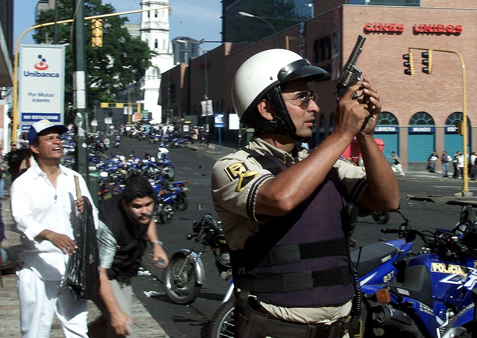 A policeman holds up his gun during clashes in Caracas April 11, 2002. At least ten people were killed and more than 80 injured as shooting broke out