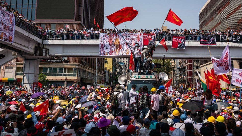 Protesters wave red NLD flags at Sule Square on February 22, 2021 in downtown Yangon, Myanmar.