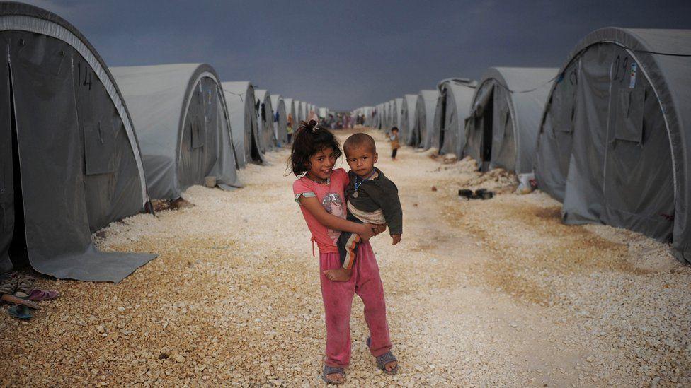 Kurdish refugee children standing among tents in refugee camp in Turkey
