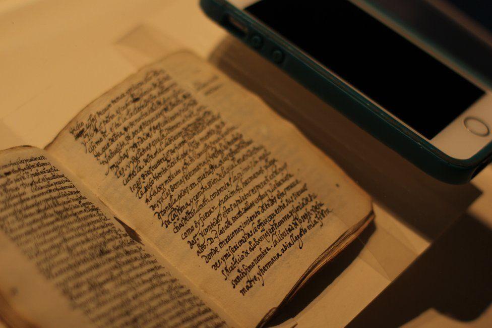 An iPhone lies next to the manuscript