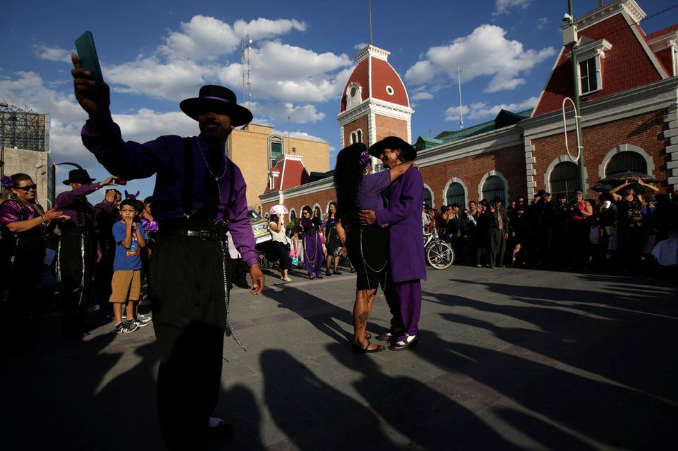 """The crowd watches a successful wedding proposal taking place between a couple dressed as """"Pachucos"""" during the Quinceanera (15th birthday) of a teenager in downtown Ciudad Juarez, Mexico, 5 August 2017."""