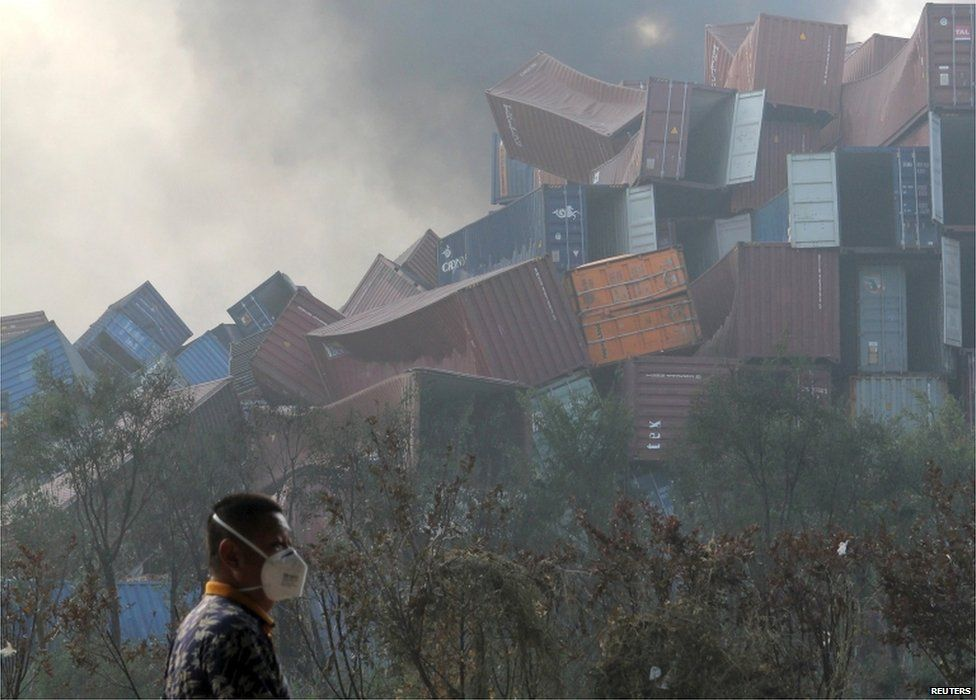 A man wearing a mask walks past overturned shipping containers after explosions hit the Binhai new district in Tianjin 13 August 2015