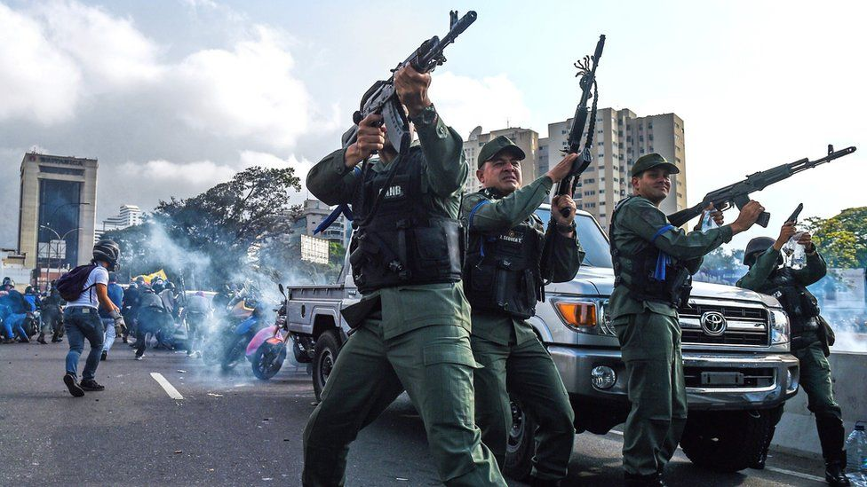 Members of the Bolivarian National Guard who joined Venezuelan opposition leader and self-proclaimed acting president Juan Guaido fire into the air to repel forces loyal to President Nicolas Maduro who arrived to disperse a demonstration near La Carlota military base in Caracas on April 30, 2019
