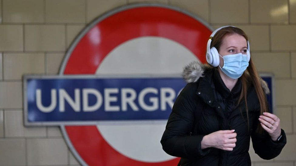 A woman wearing a mask stands in front of a London Underground sign