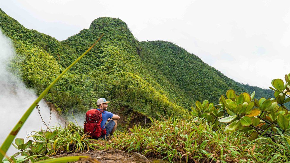 A man on a green mountainside in Dominica