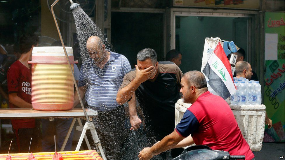 Iraqis cool off at a roadside stall in Baghdad, 20 July 2016