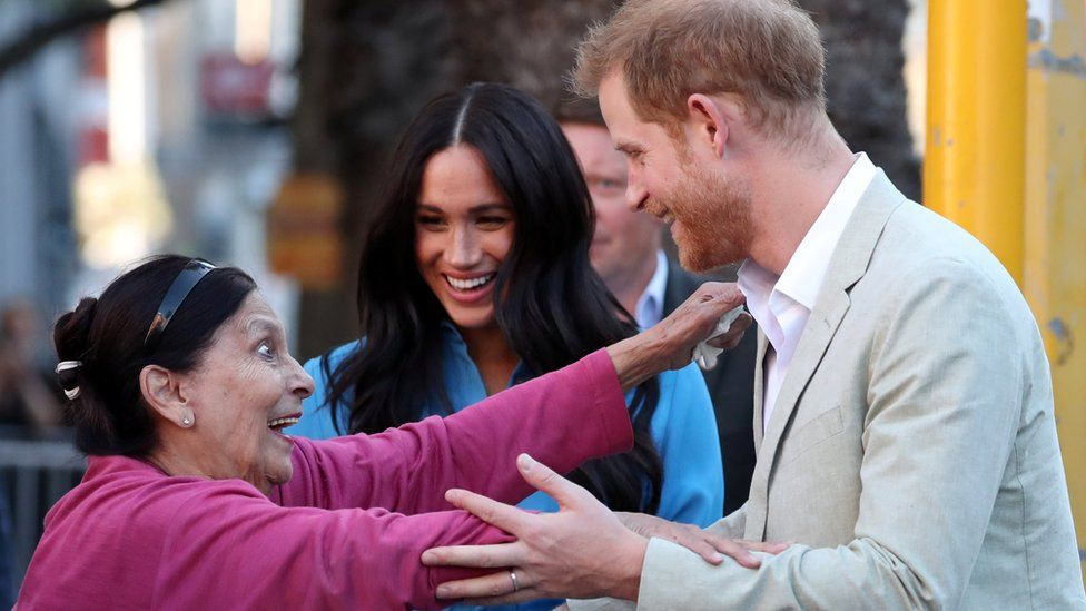 A wide-eyed woman reaches out to Prince Harry