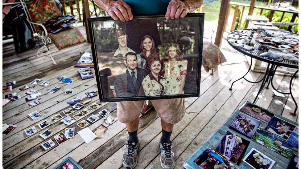 """Hilton Pray, 82, holds on to one of his thousands of photographs that were damaged and now drying after an estimated 4 feet of water filled his home off of Greenwell Springs. He had an entire village he had built behind his home, starting in 1995, that featured a general store, a chapel, and countless antiques and mementos of his life as a collector, all lost. In his daughter's words, """"He put mama in the highest lawnmower we had, and went back for her insulin"""", Denham Springs, LA"""