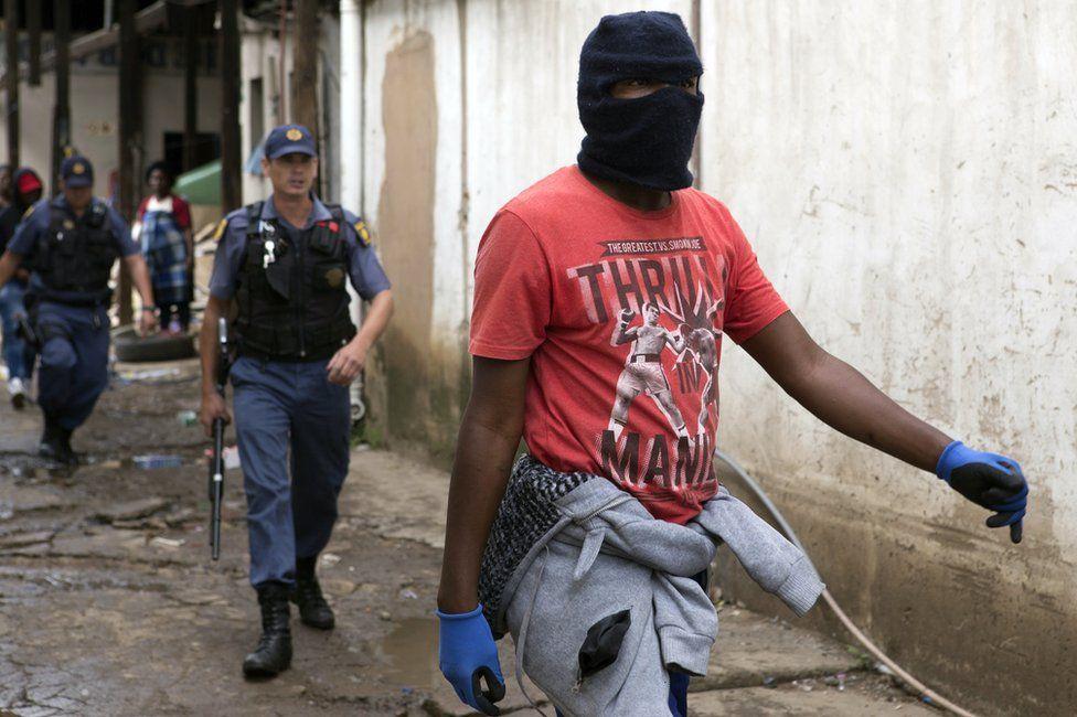 SA national wearing balaclava and carrying a rock walks ahead of an armed policeman