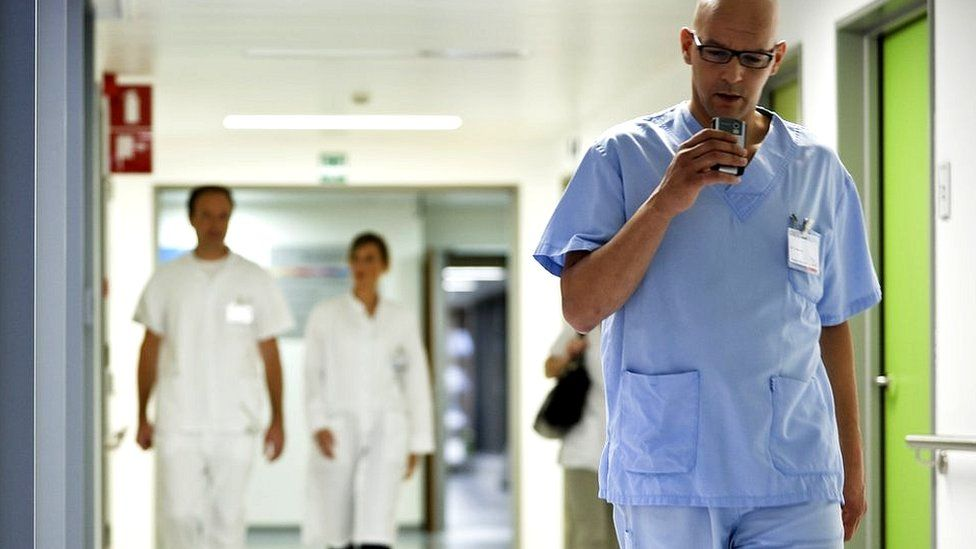 Doctor walking while dictating notes in GP surgery
