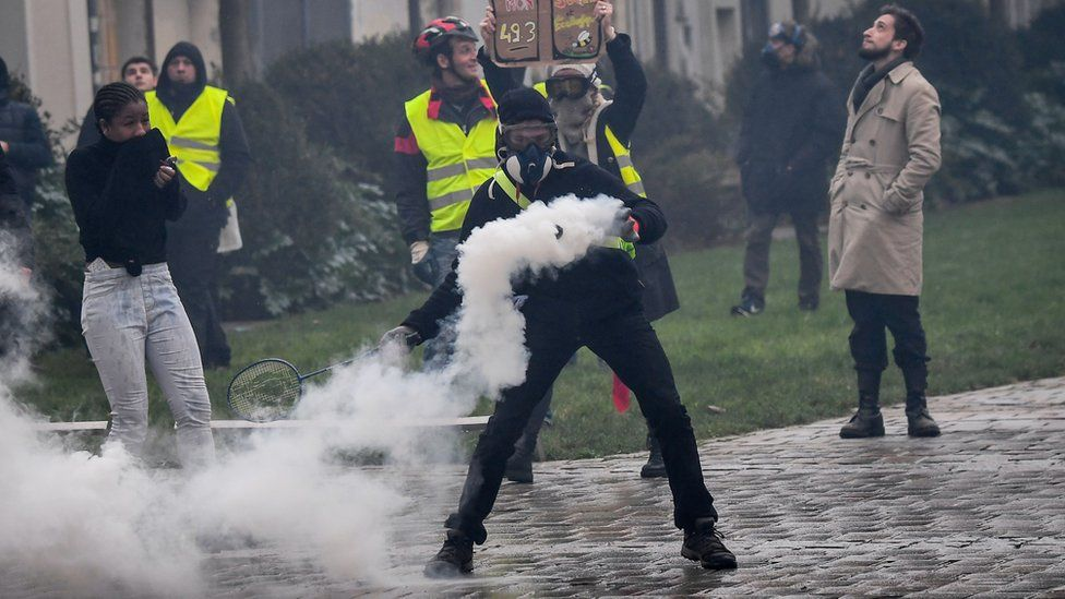 A protester - wearing a soon-to-be-banned face covering - throws back a police gas canister on 19 January