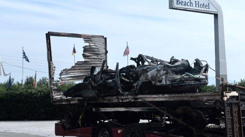 The burned-out car is retrieved near Kavala