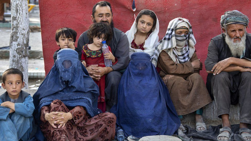 Charyar,70, from the Balkh province sits alongside his family at a makeshift IDP camp in Share-e-Naw park