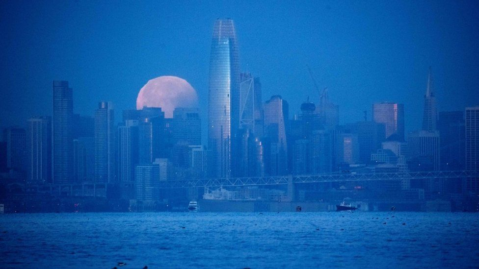 Moon is pictured setting behind San Francisco skyline