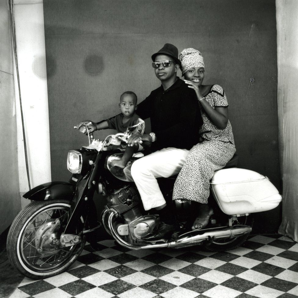 A family on a motorbike in a photo studio in Mali