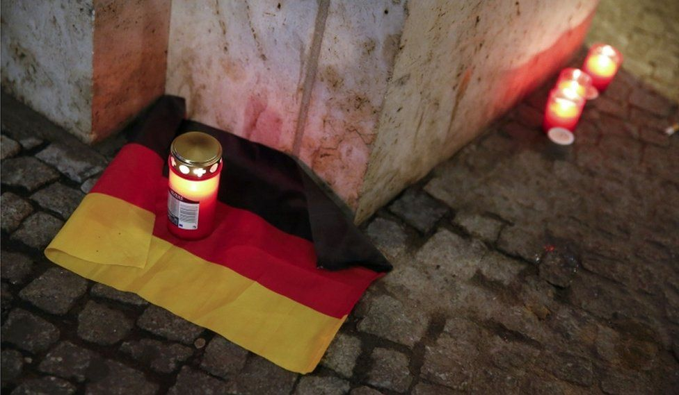 A candle burns on a German national flag near the site where a truck ploughed through a crowd at a Berlin Christmas market