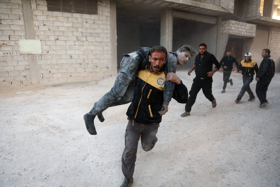 White helmets rescue an injured fighter in a Damascus suburb in 2017