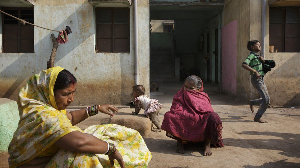 Two Indian women sat opposite each other on the pavement in an Indian village. A boy runs behind them in the background.