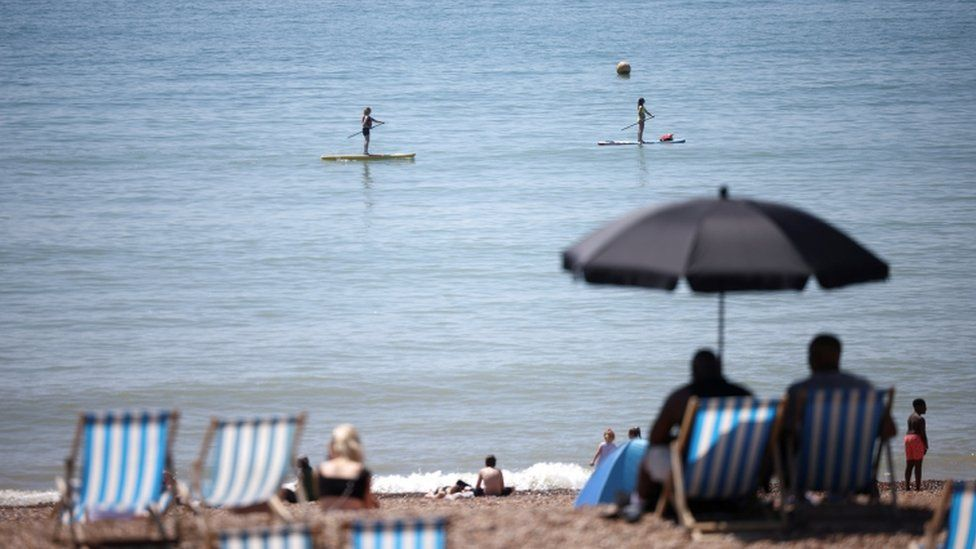 People paddle board as they enjoy the hot weather at Brighton beach