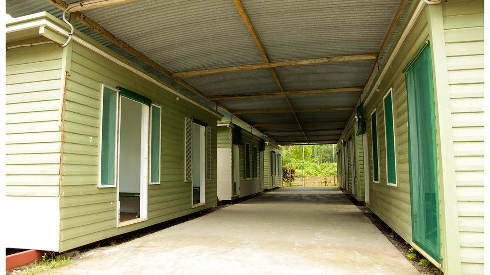 Handout photo showing six wooden huts on Manus in October 2012