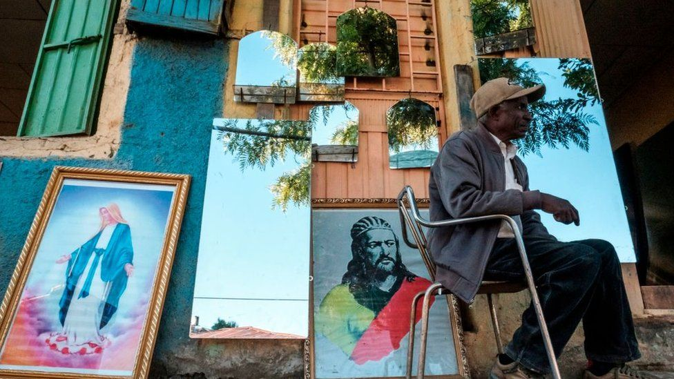 A man seats in front of a shop selling mirrors and paintings in Gondar, Ethiopia, on November 23, 2020.