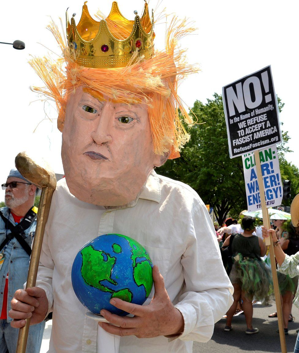 A protester in a costume depicting Trump holds an Earth and a golf club as he joins demonstrators moving down Pennsylvania Avenue during a People's Climate March,