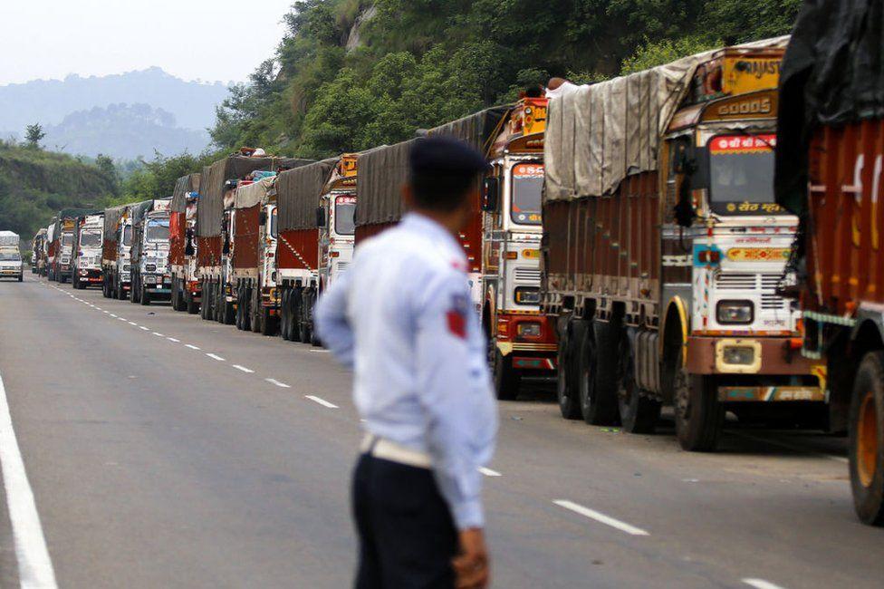 A policeman looks at trucks stranded on the Jammu-Srinagar highway in Nagrota, near Jammu, on August 9, 2019,