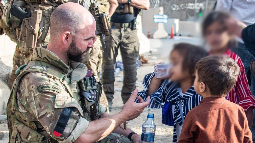 British solider offers water to child at Kabul airport on 23 August 2021